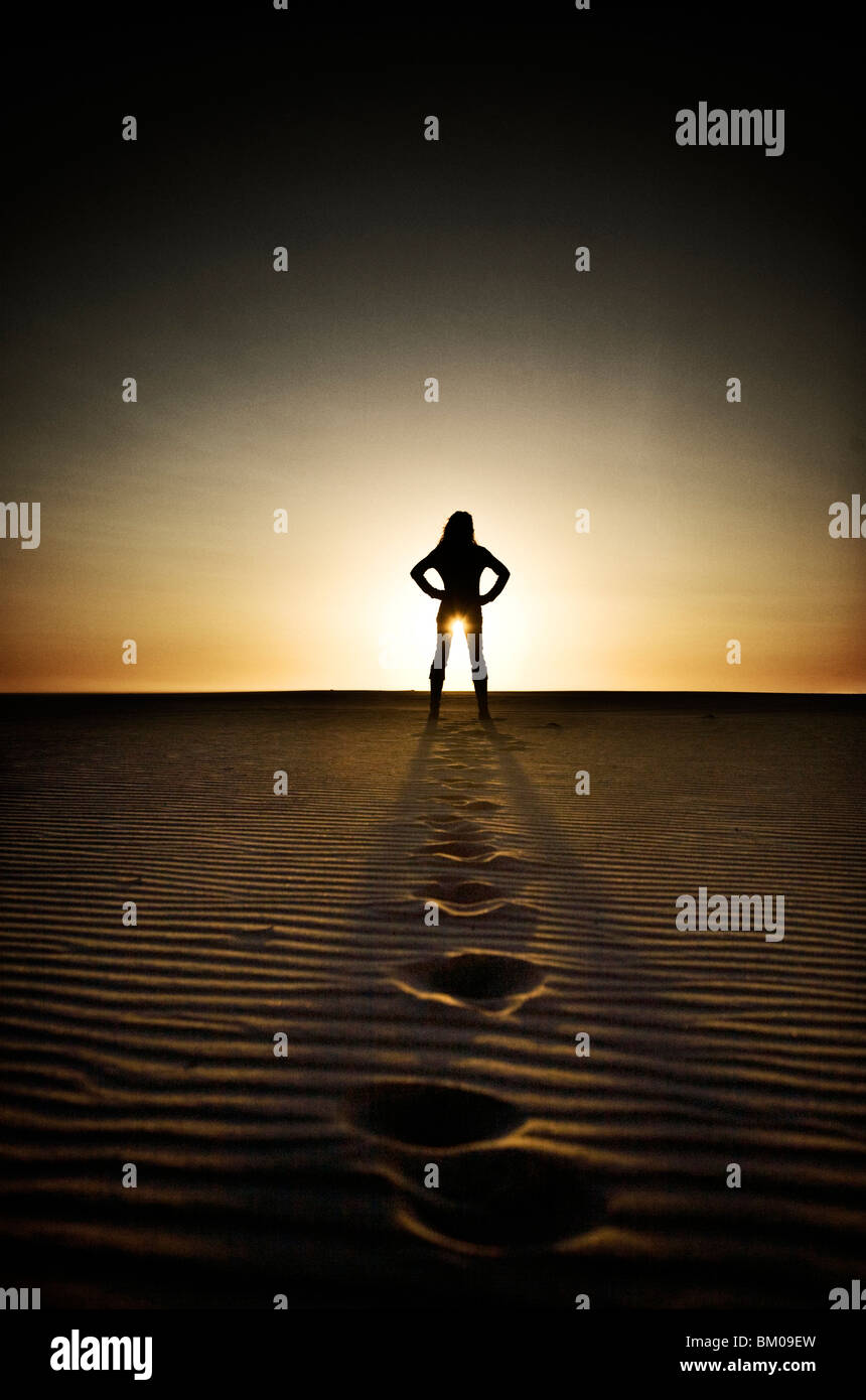 Young woman in distance standing on beach at sunset with foot prints in sand - Stock Image