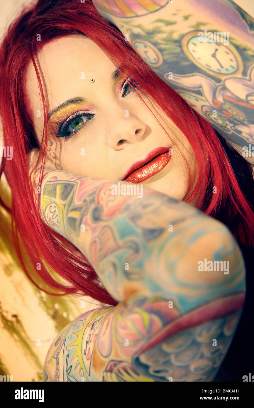 Closeup of a woman with bright red hair and green eyes with her arms covered in colorful tattoos - Stock Image