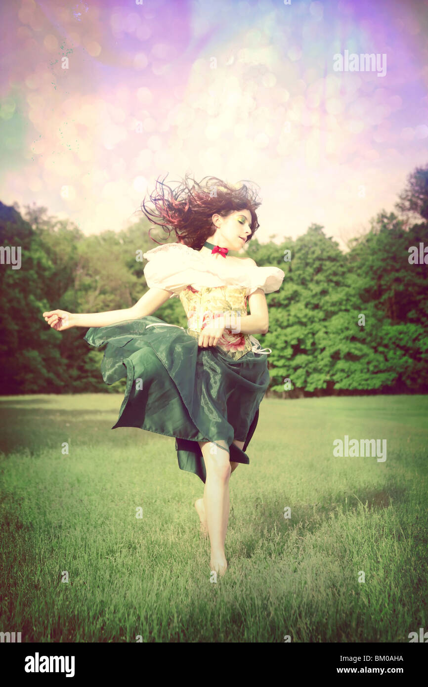 Prancing girl in a field with windblown hair and a floral dress - Stock Image