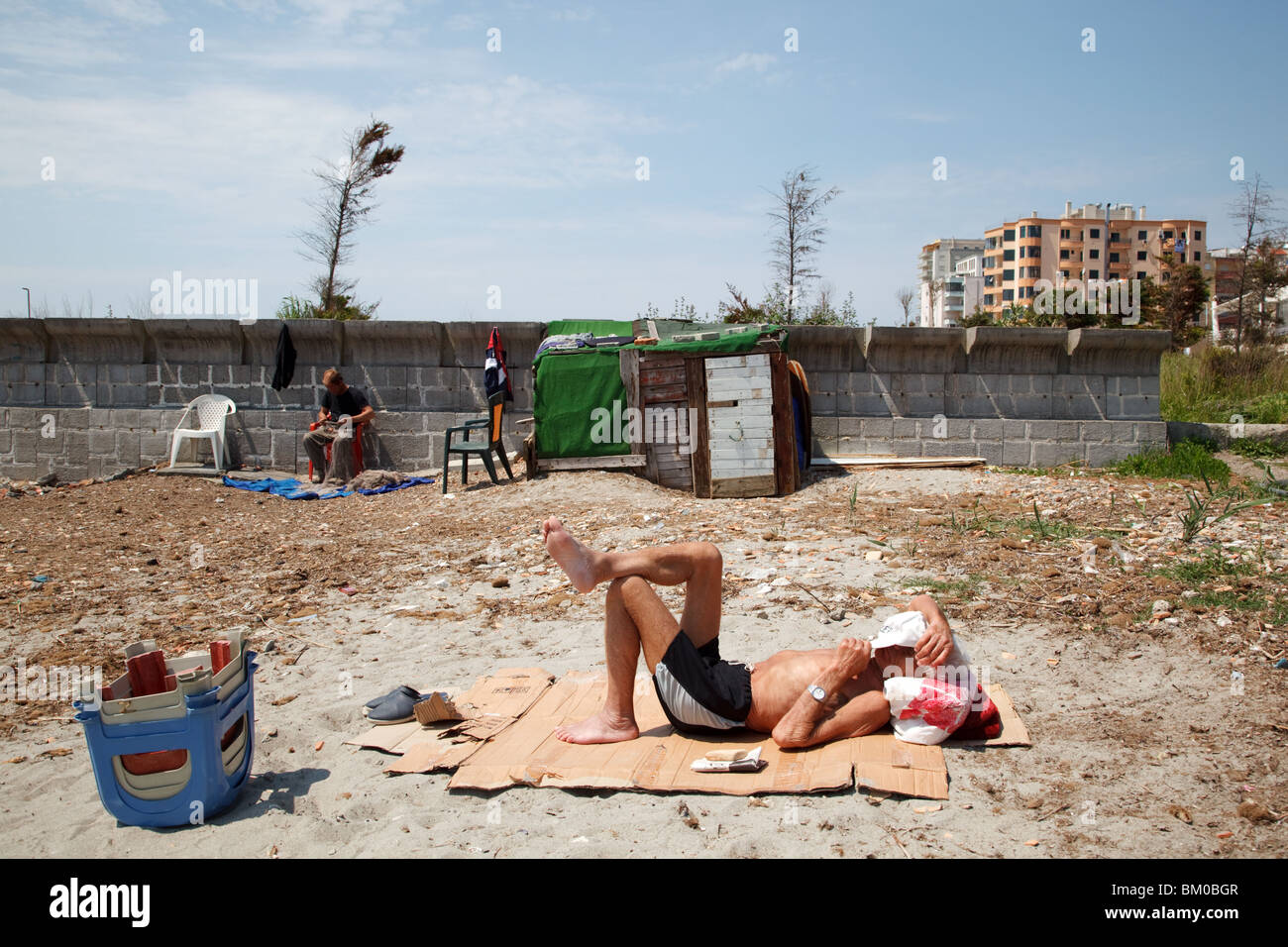 A man sunbathes on a beach in Durres, Albania. - Stock Image