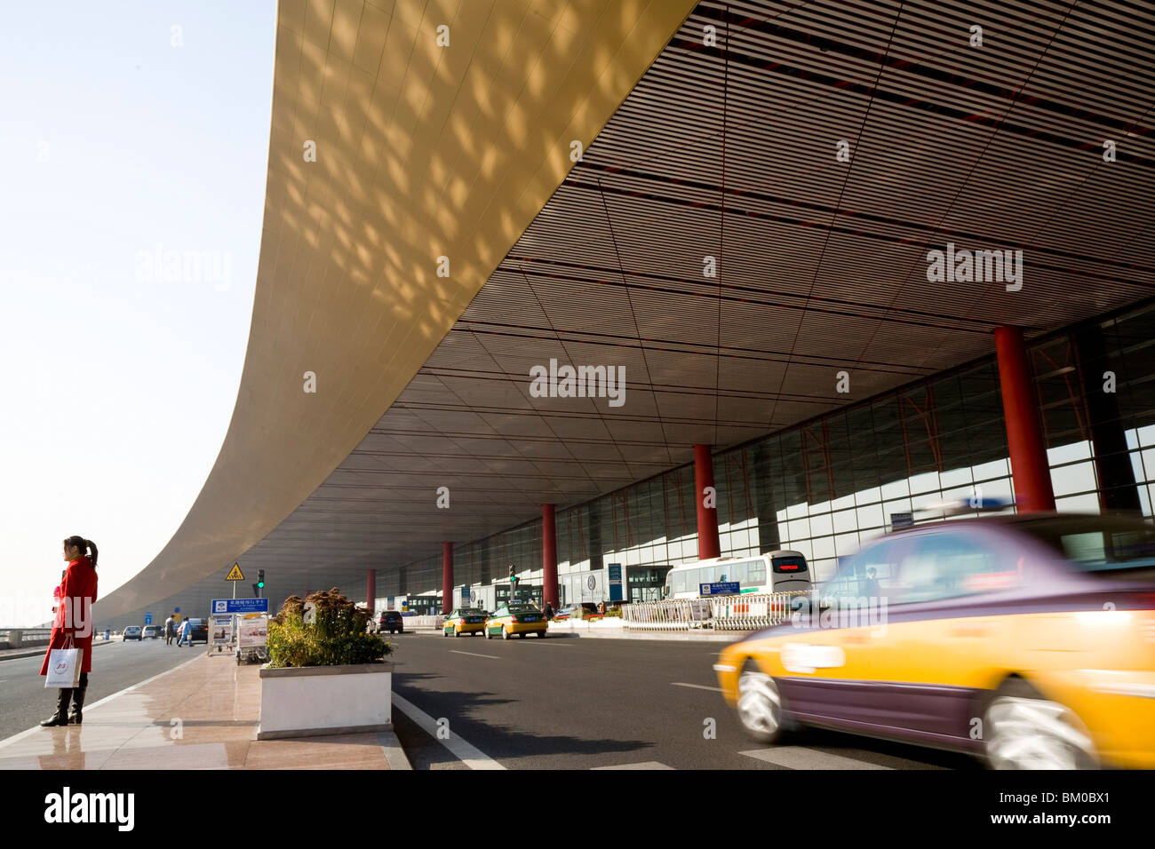 Woman and taxi in front of the International Airport Beijing, largest building in the world, Peking, China, Asia - Stock Image