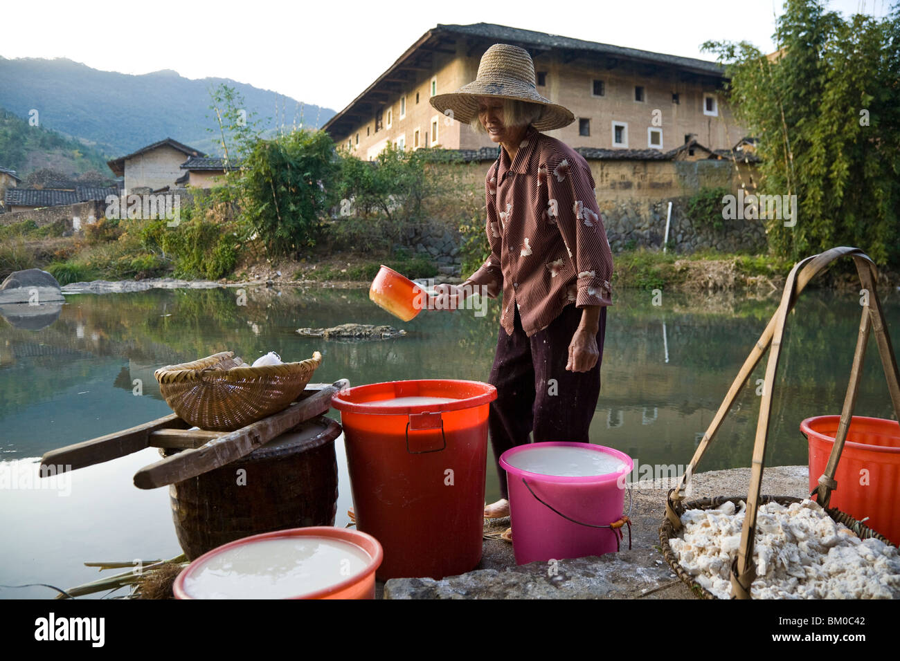 Chinese farmer fetching water from a small stream, village of the Hakka, Hongkeng, Longyan, Fujian, China, Asia - Stock Image
