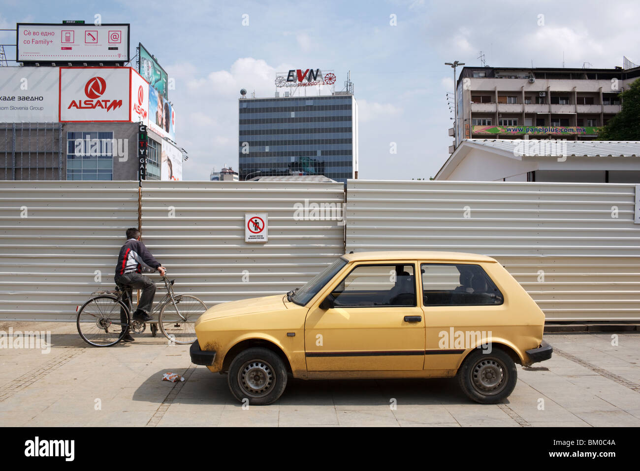 A man on a bicycle and yellow Yugo car parked in central Skopje, Macedonia. - Stock Image