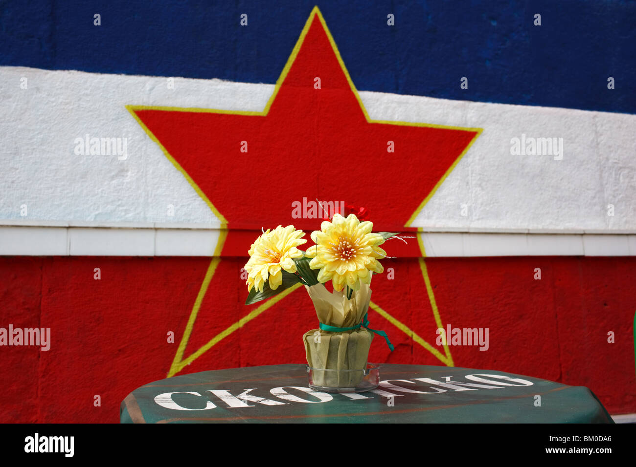Restaurant table with a former Yugoslavia flag painted on the wall in Skopje, Macedonia. - Stock Image