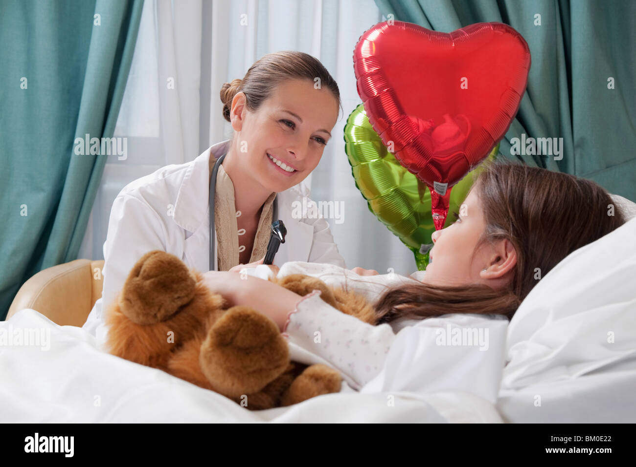 Female doctor talking with a girl in a hospital ward - Stock Image