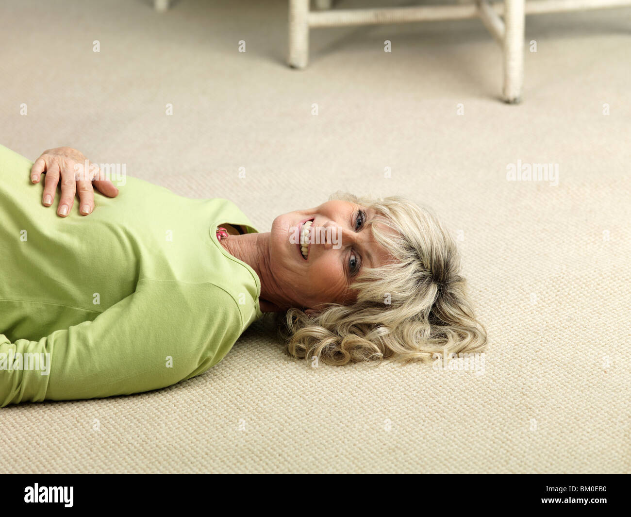 Mature pregnant woman lying on floor - Stock Image