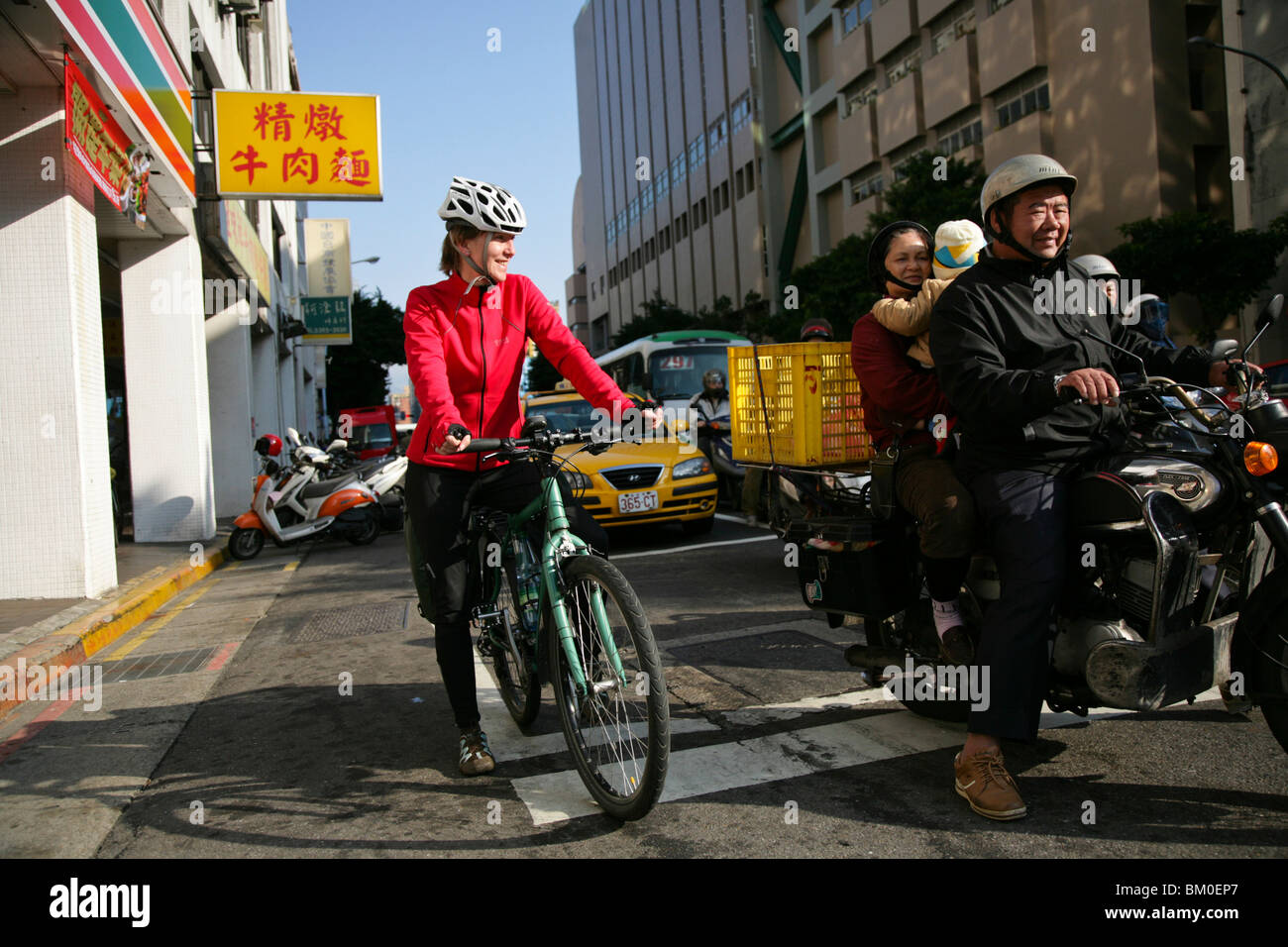 Young German woman on bicycle and family on motorbike, Taipei, Republic of China, Taiwan, Asia - Stock Image