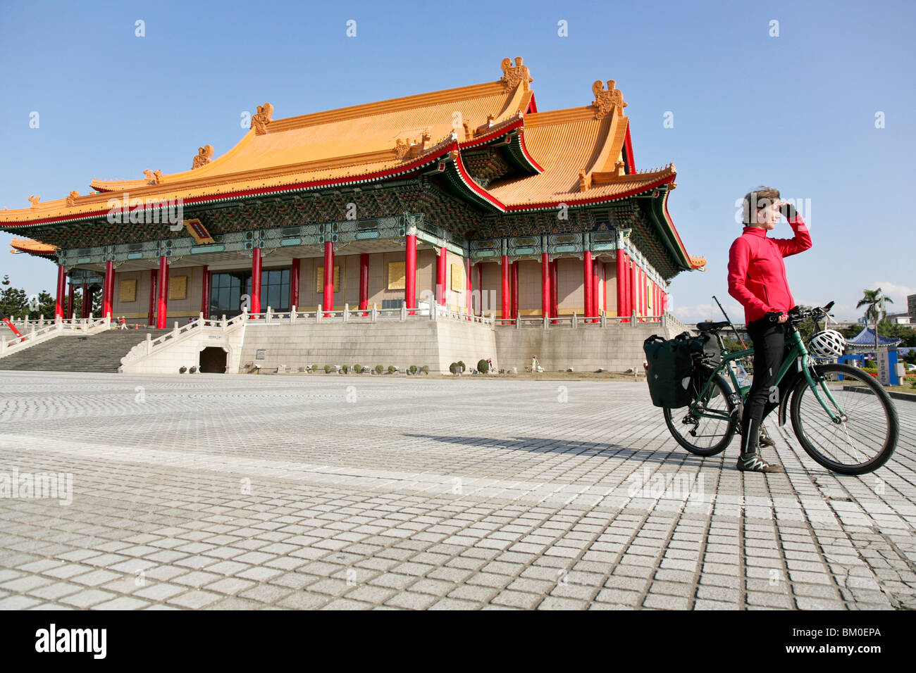 Young German woman on bicycle in front of National Theatre and National Concert Hall, Taipei, Republic of China, - Stock Image