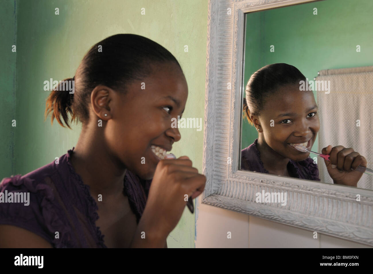 Teenage girl (16-17) brushing teeth, Cape Town, Western Cape Province, South Africa - Stock Image