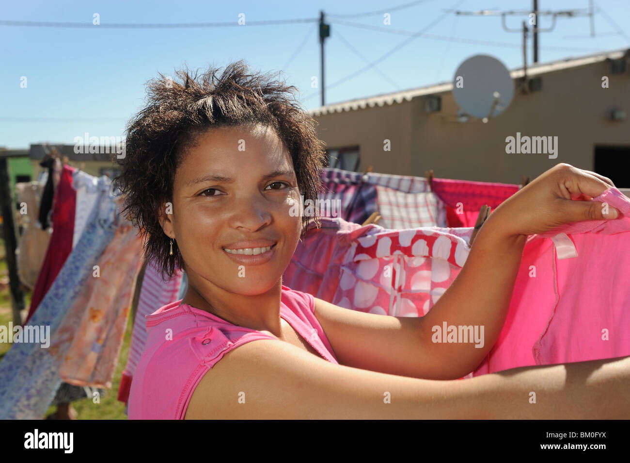 Woman hanging up laundry, St Francis Bay, Sea Vista, Eastern Cape Province, South Africa - Stock Image