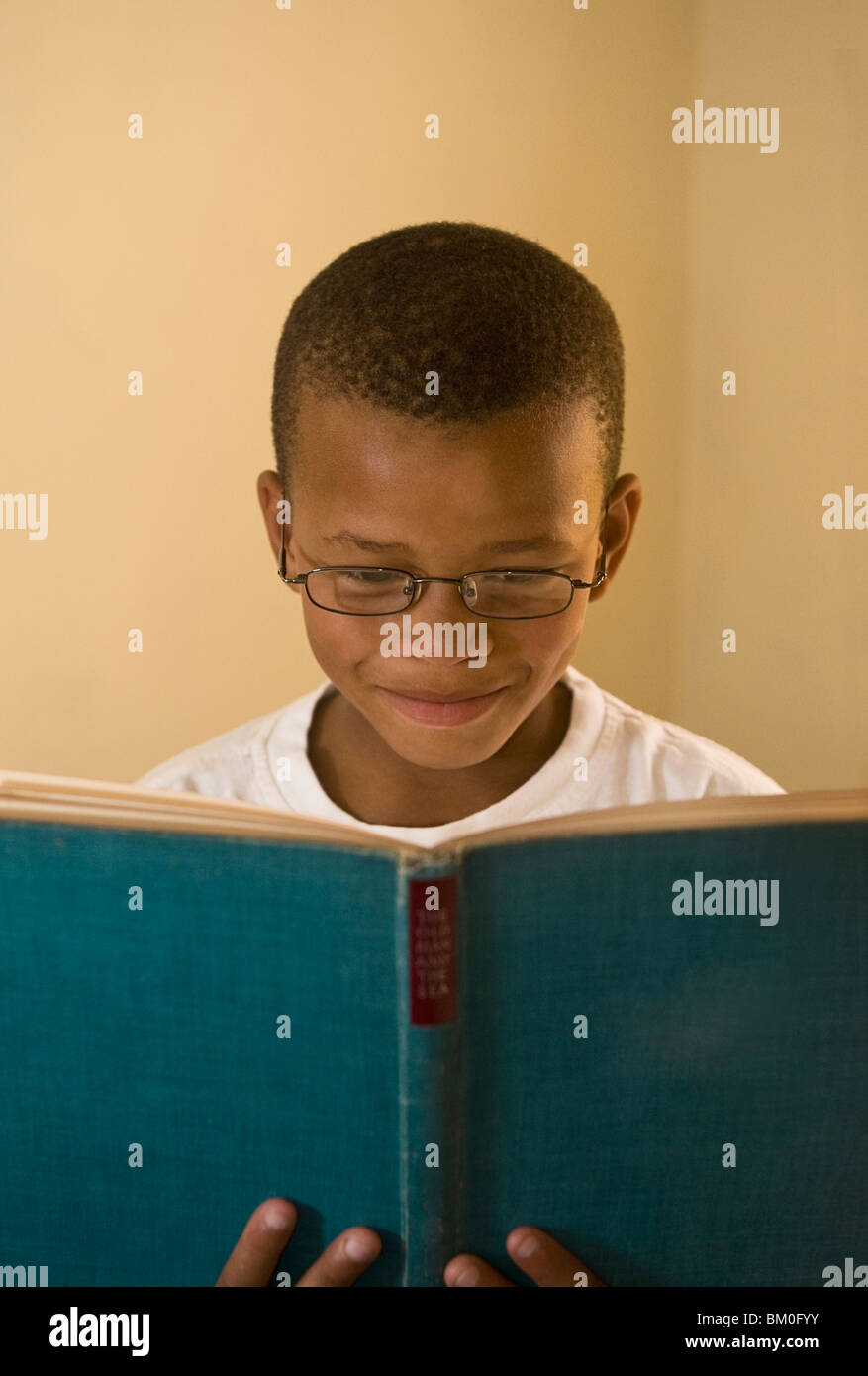 Boy (8-9) smiling while reading book, St Francis Bay, Sea Vista, Eastern Cape Province, South Africa - Stock Image