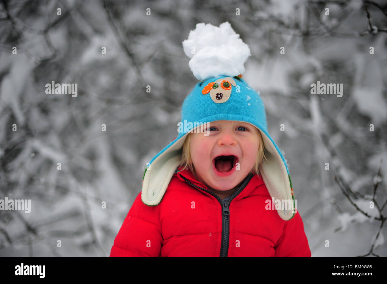 a young boy playing in the winter snow with a giant snowball on top his hat bobble hat - Stock Image
