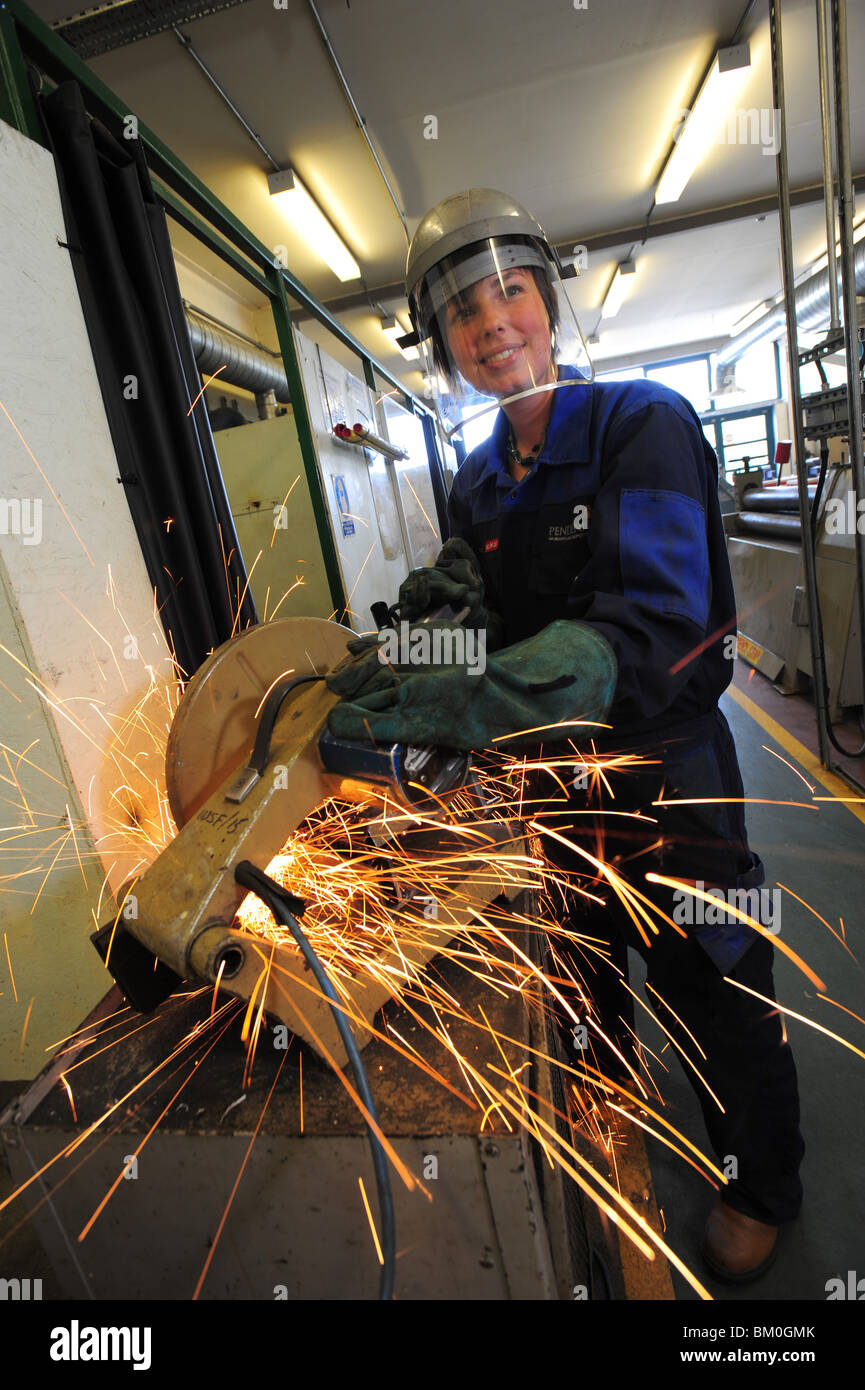 a female engineering student using an angle grinder, creating sparks in a workshop - Stock Image