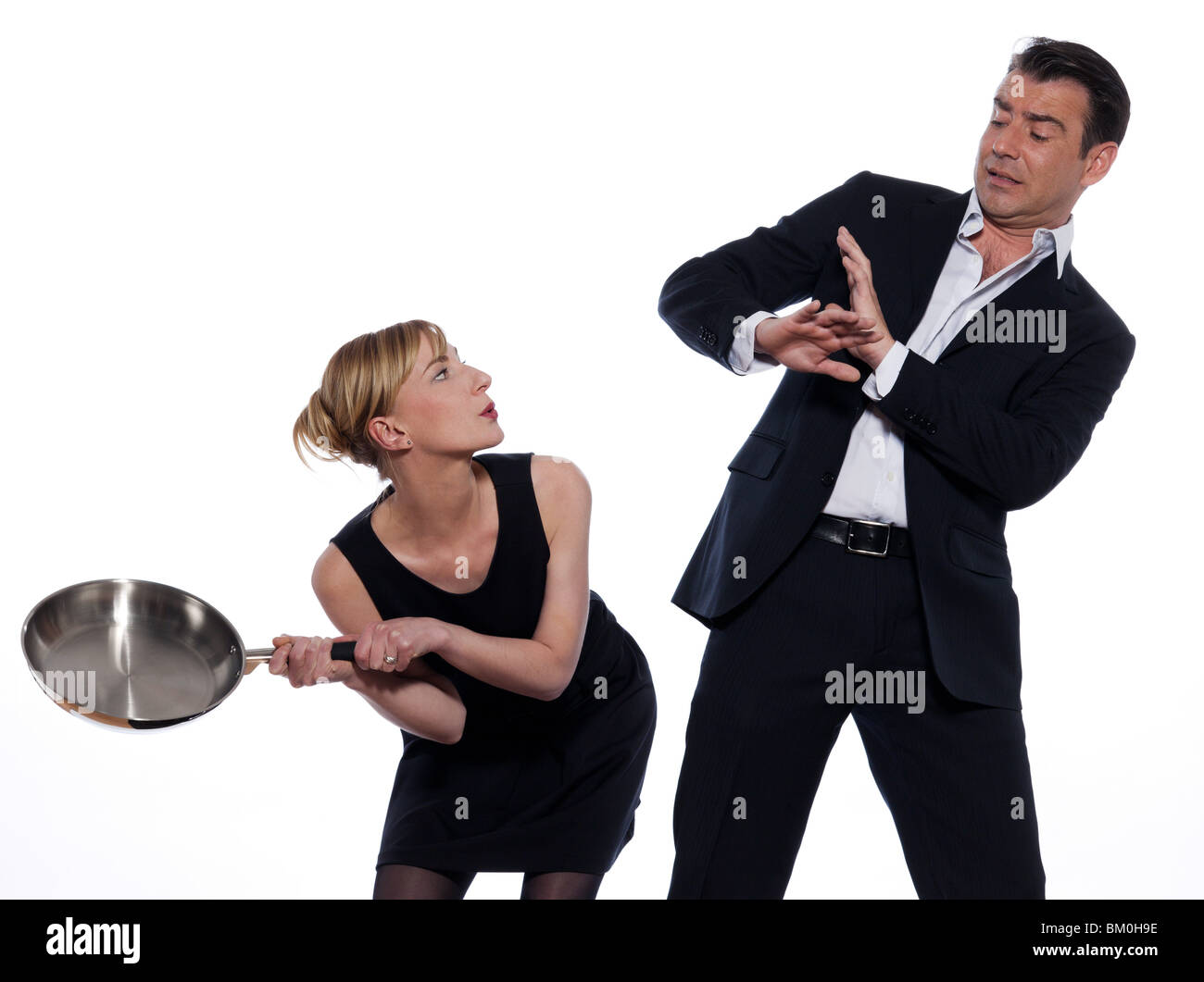 beautiful caucasian couple on studio white background in funny conflict - Stock Image