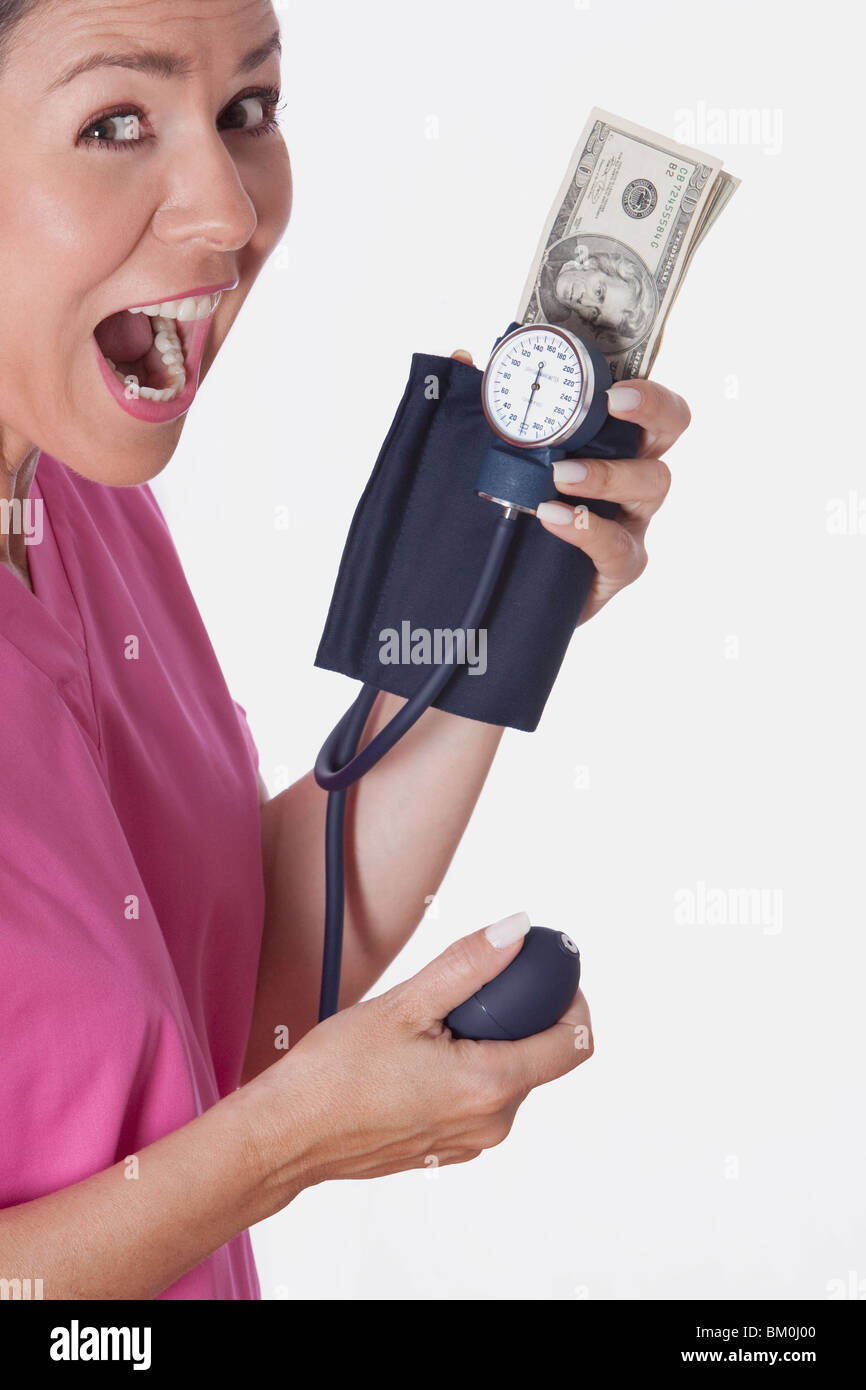 Female doctor holding a blood pressure gauge with currency notes - Stock Image