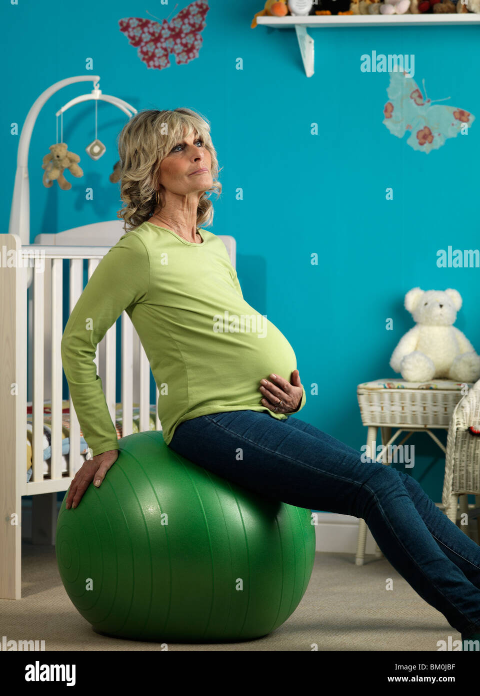 Pregnant older woman exercising - Stock Image