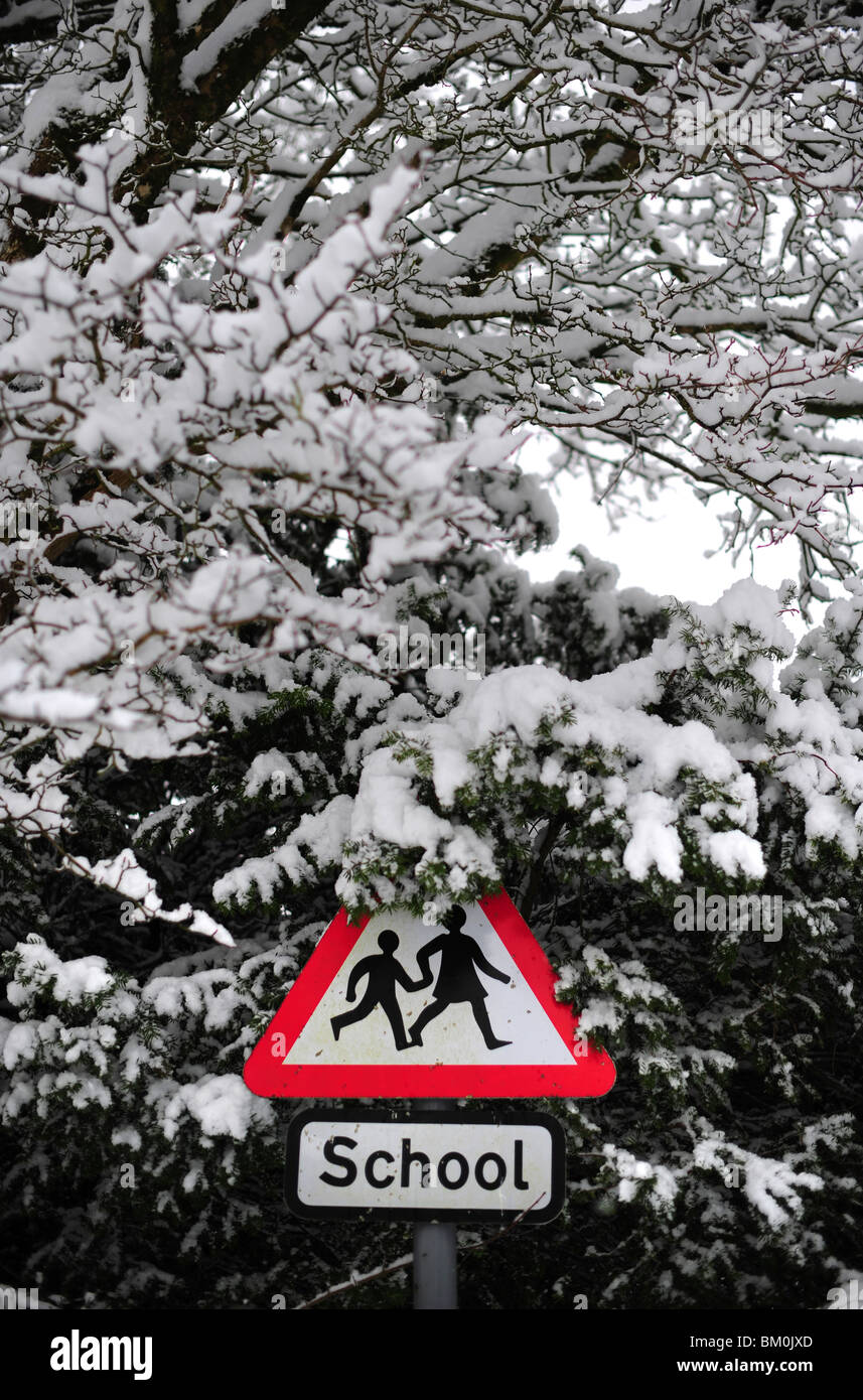 A school sign covered around with snow, illustrating schools being closed during deep and heavy snow - Stock Image