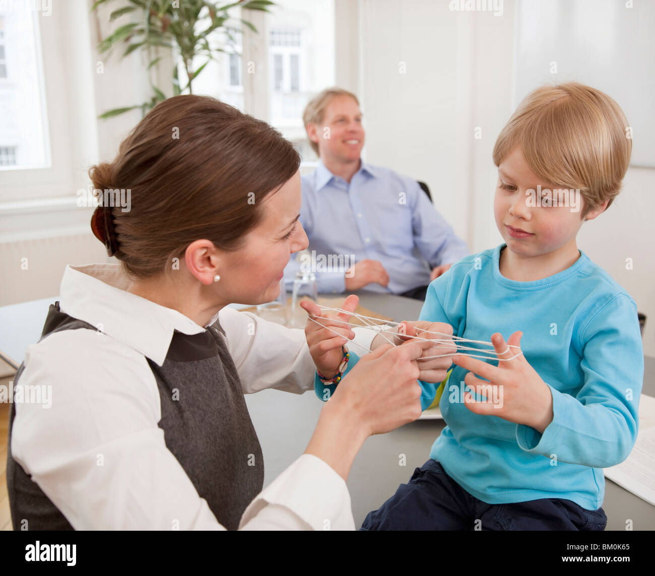 Businesswoman, boy playing string game Stock Photo
