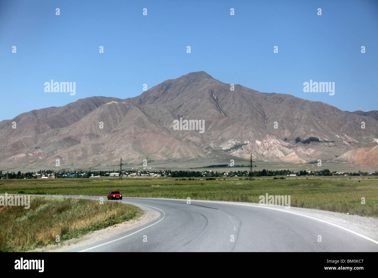 A paved road sweeps past mountains in Kyrgystan, Central Asia. - Stock Image