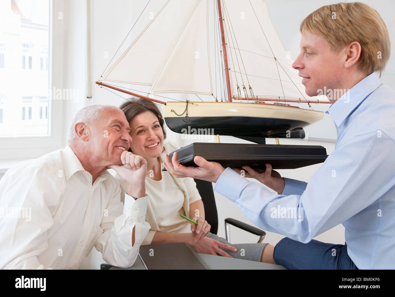 Businesspeople looking at model ship Stock Photo