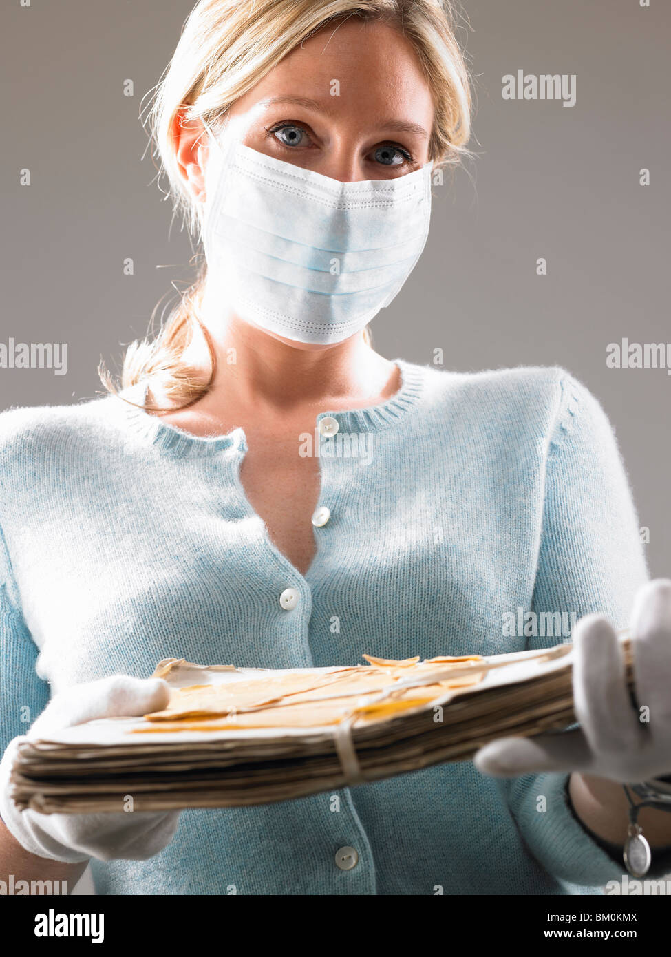 Woman with mask, holding precious files - Stock Image
