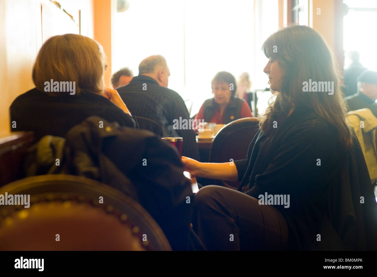 Tables of people talking in brightly-lit café - Stock Image