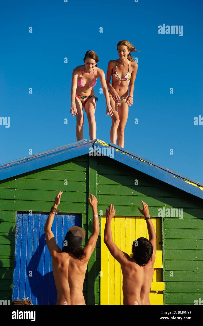 Girls about to climb off beach hut roof - Stock Image