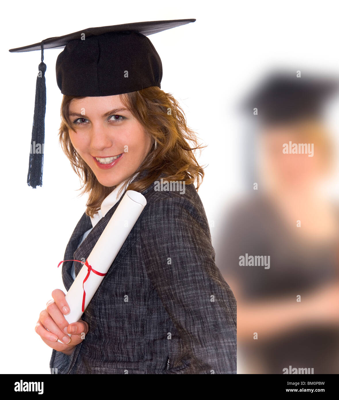 Young woman with graduation diploma and graduation hat, second graduate student blurry in background - Stock Image