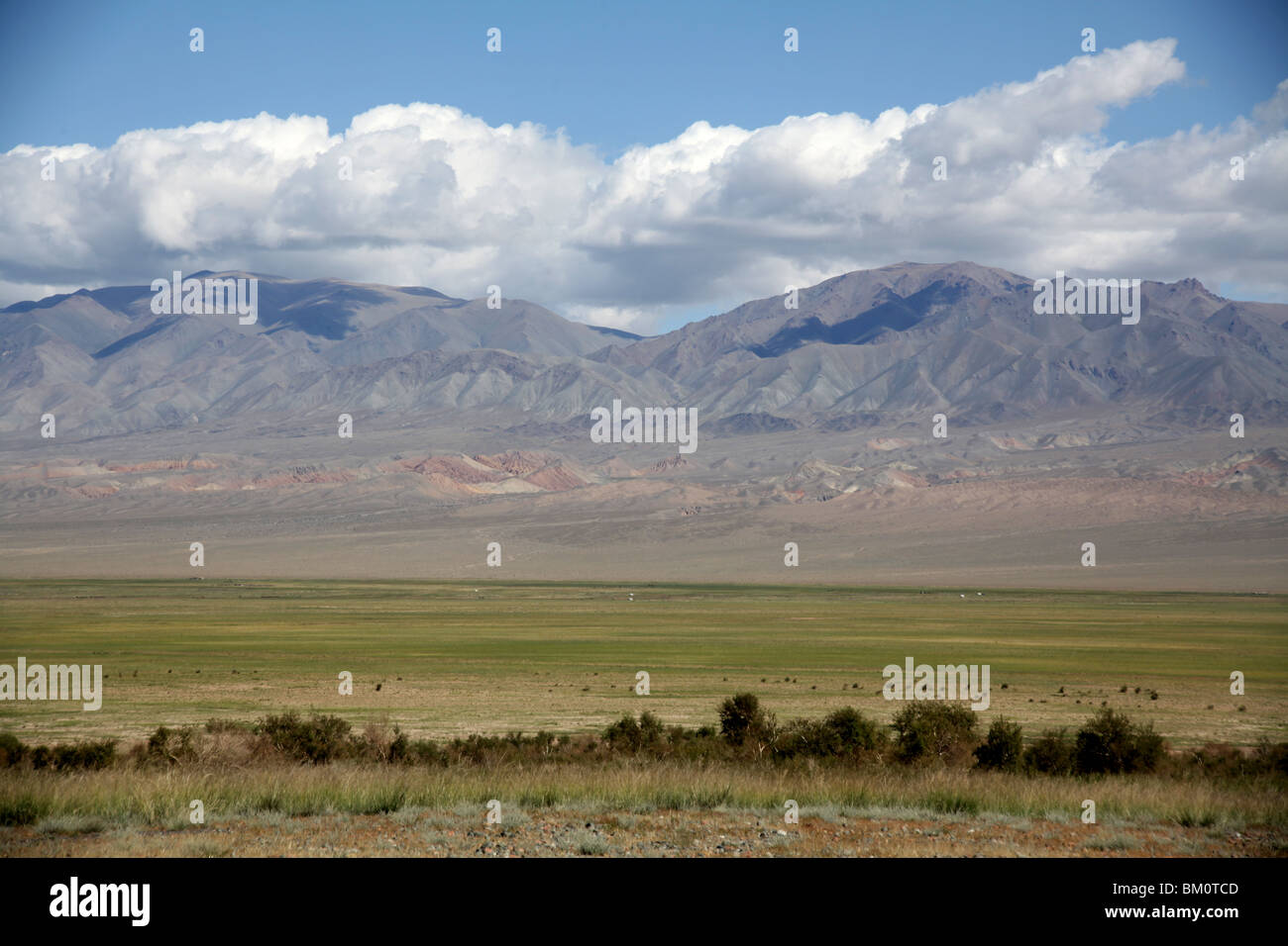 Mountains loom over the mongolian Steppe in Mongolia. - Stock Image