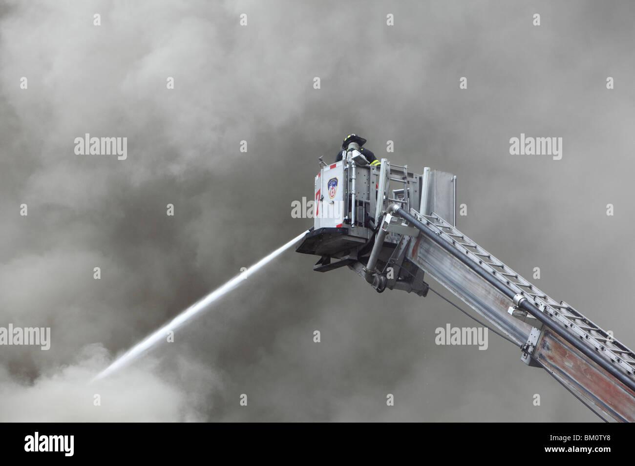 firefighter battling a smoky fire Stock Photo