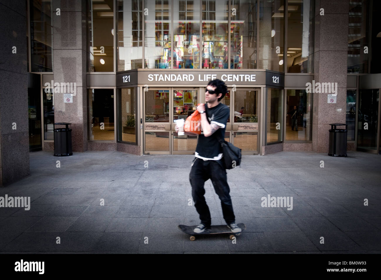 A man on a skateboard rides in front of a the Standard Life Centre in Toronto financial district - Stock Image