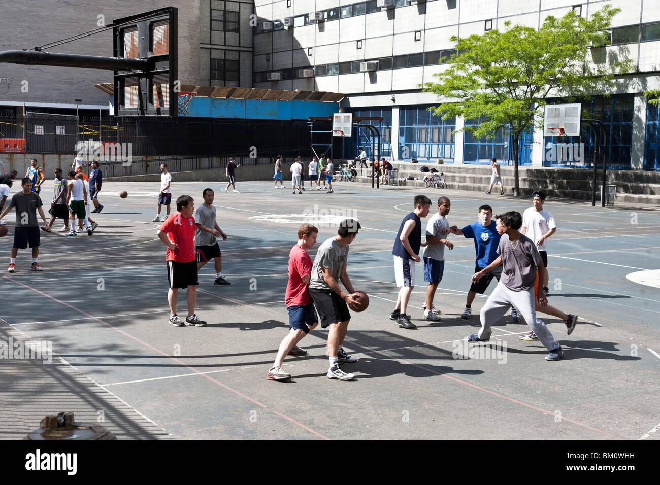 multiethnic street basketball game underway in spring sunshine on high school playground in 'Hells Kitchen' - Stock Image