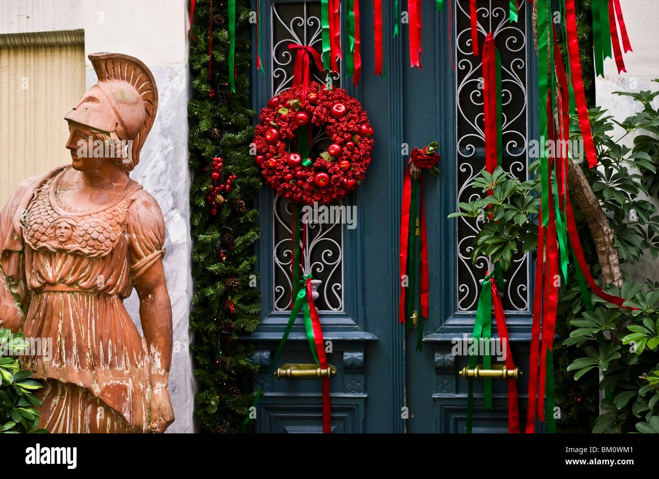 A garden statue of goddess Athina with her back turned to a door of a house in Plaka which is decorated with Christmas - Stock Image