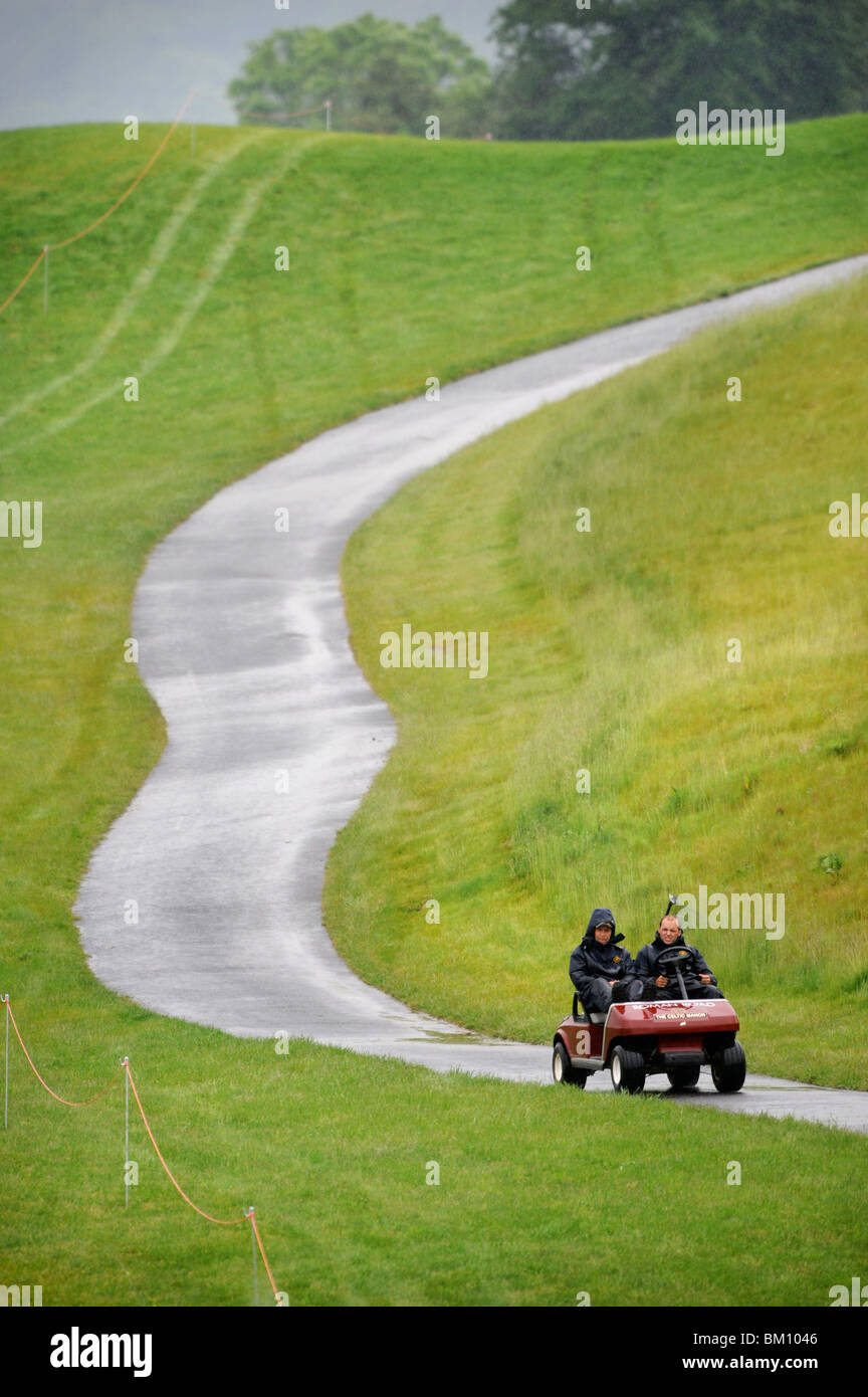 Two groundsmen ride a golf buggy in the rain at the Celtic Manor Wales Open 2008 - Stock Image