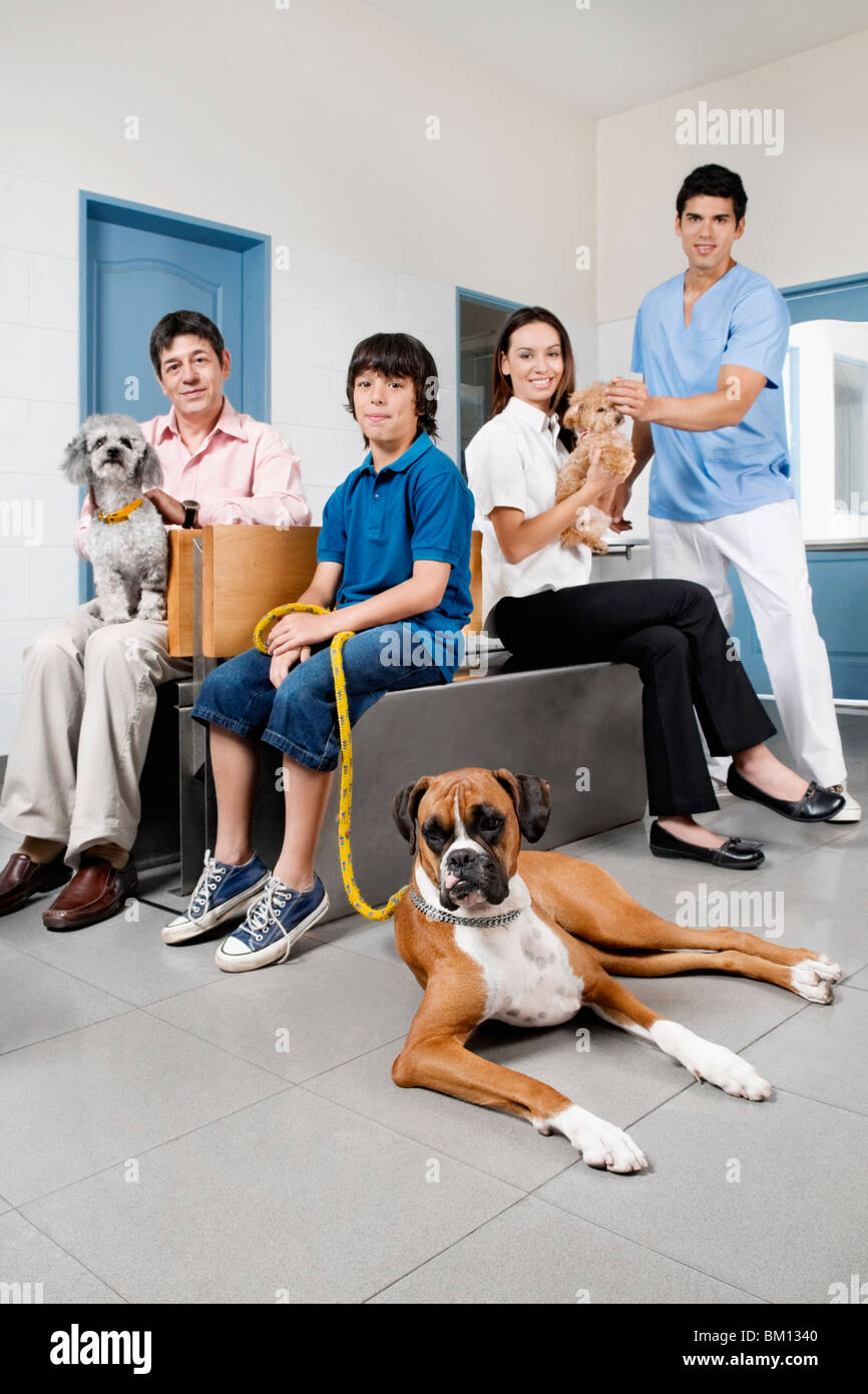 Pets with their owners in a veterinary hospital - Stock Image