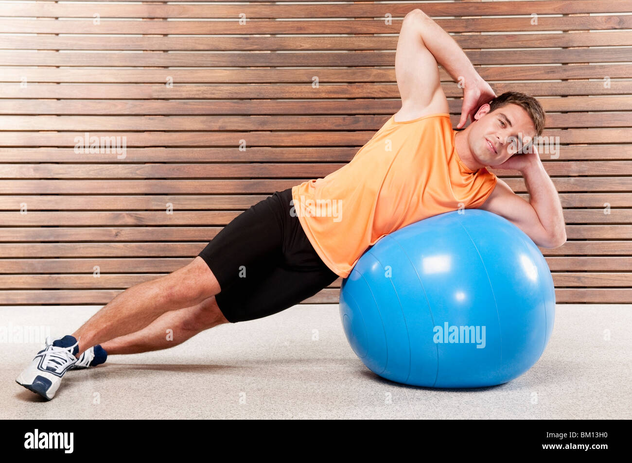 Man exercising on a fitness ball in a gym - Stock Image