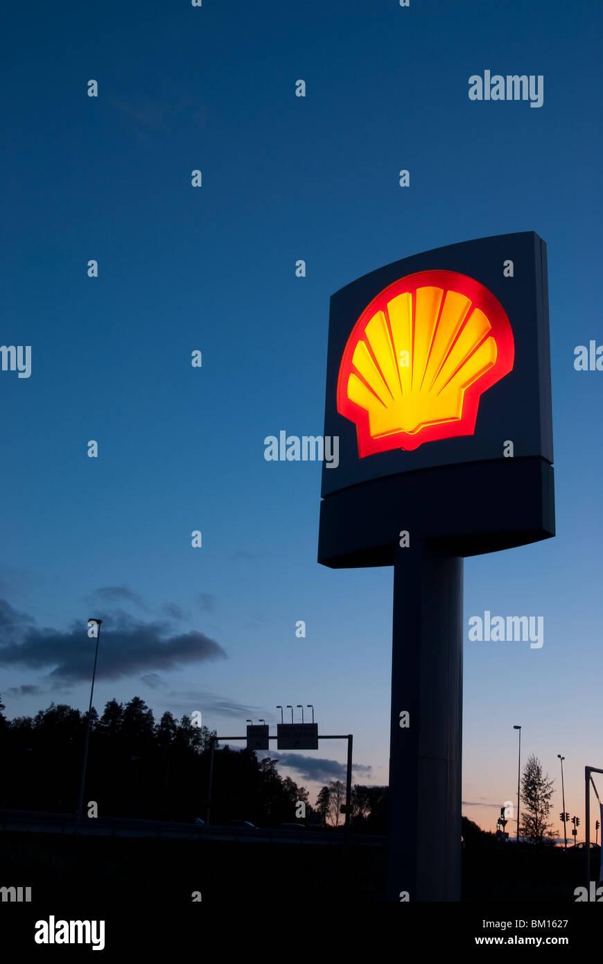 Illuminated Shell Oil sign at civil twilight - Stock Image