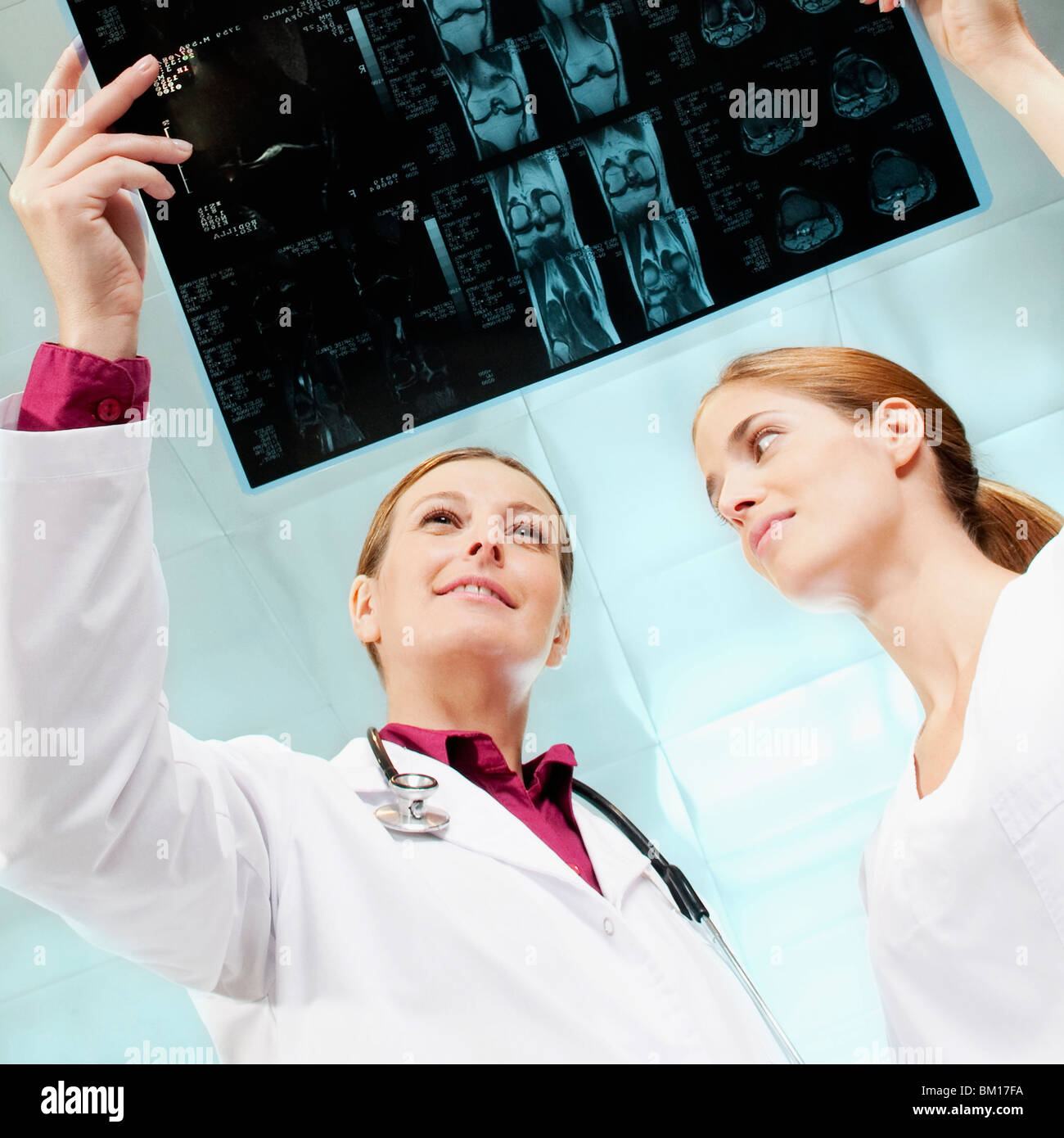 Female doctor and a nurse examining an X-Ray - Stock Image