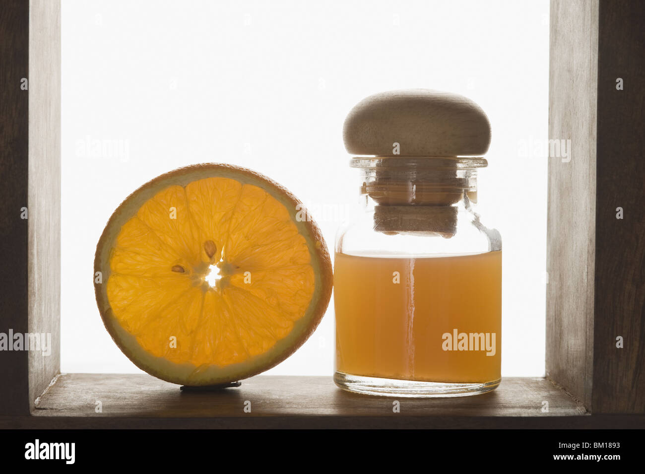 Close-up of therapeutic oil with an orange half - Stock Image