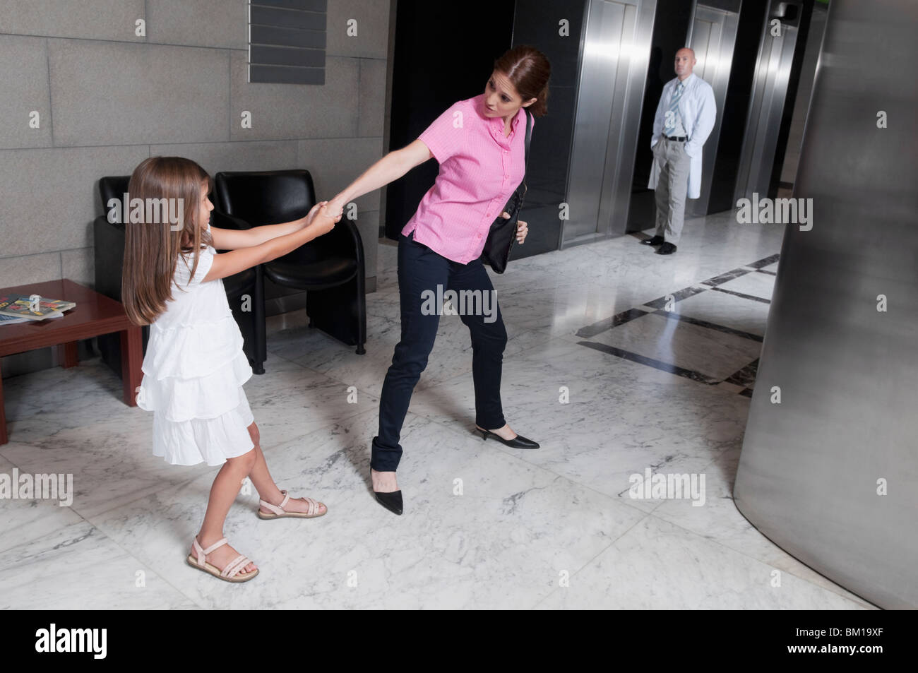 Girl tugging her mother in a hospital - Stock Image