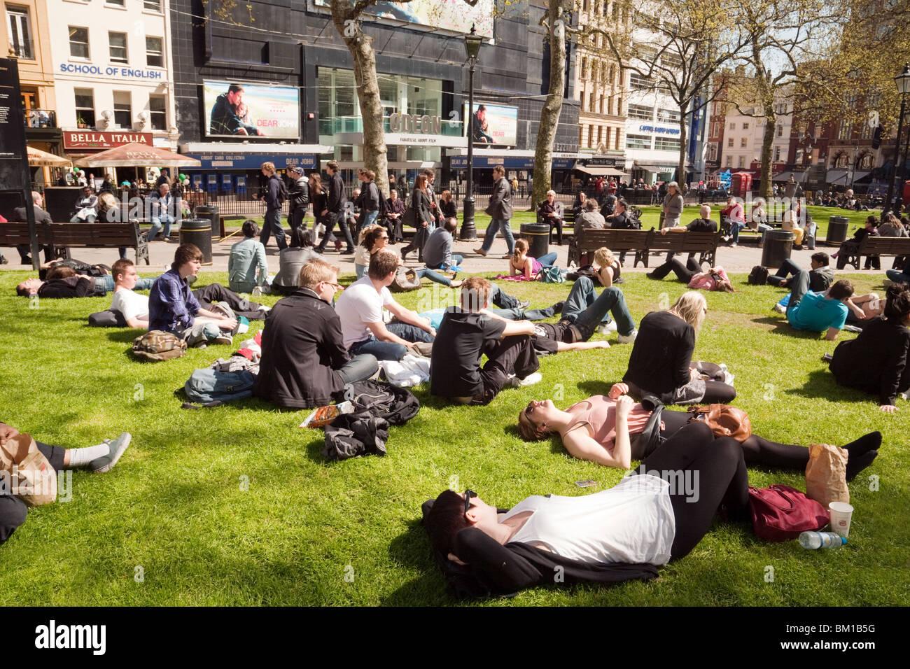 Teenagers sitting on the grass enjoying the sunshine, Leicester Square, London UK - Stock Image