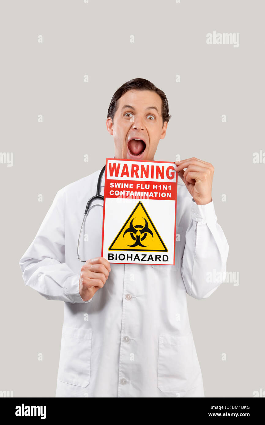 Portrait of a doctor showing a Biohazard warning sign - Stock Image