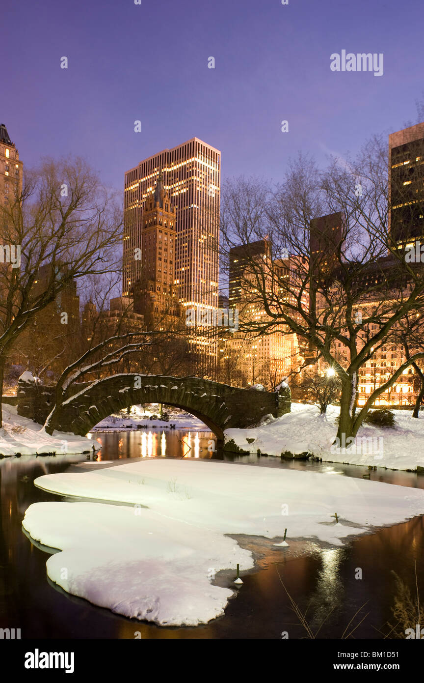A view of the Gapstow Bridge in Central Park and city skyline at dusk after a snow storm, New York City, New York Stock Photo