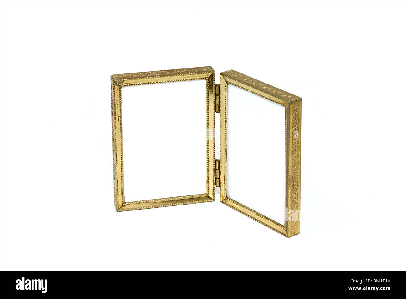 an antique bi-fold gold tone picture frame open at an angle Stock ...