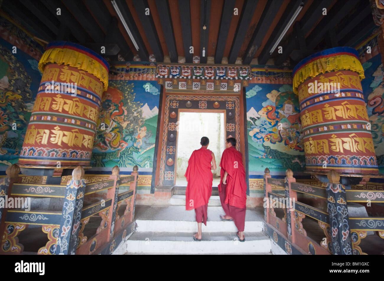 Monks walking between prayer wheels at Trongsa Dzong (Chokhor Raptentse) dating from 1648, Bhutan Asia - Stock Image