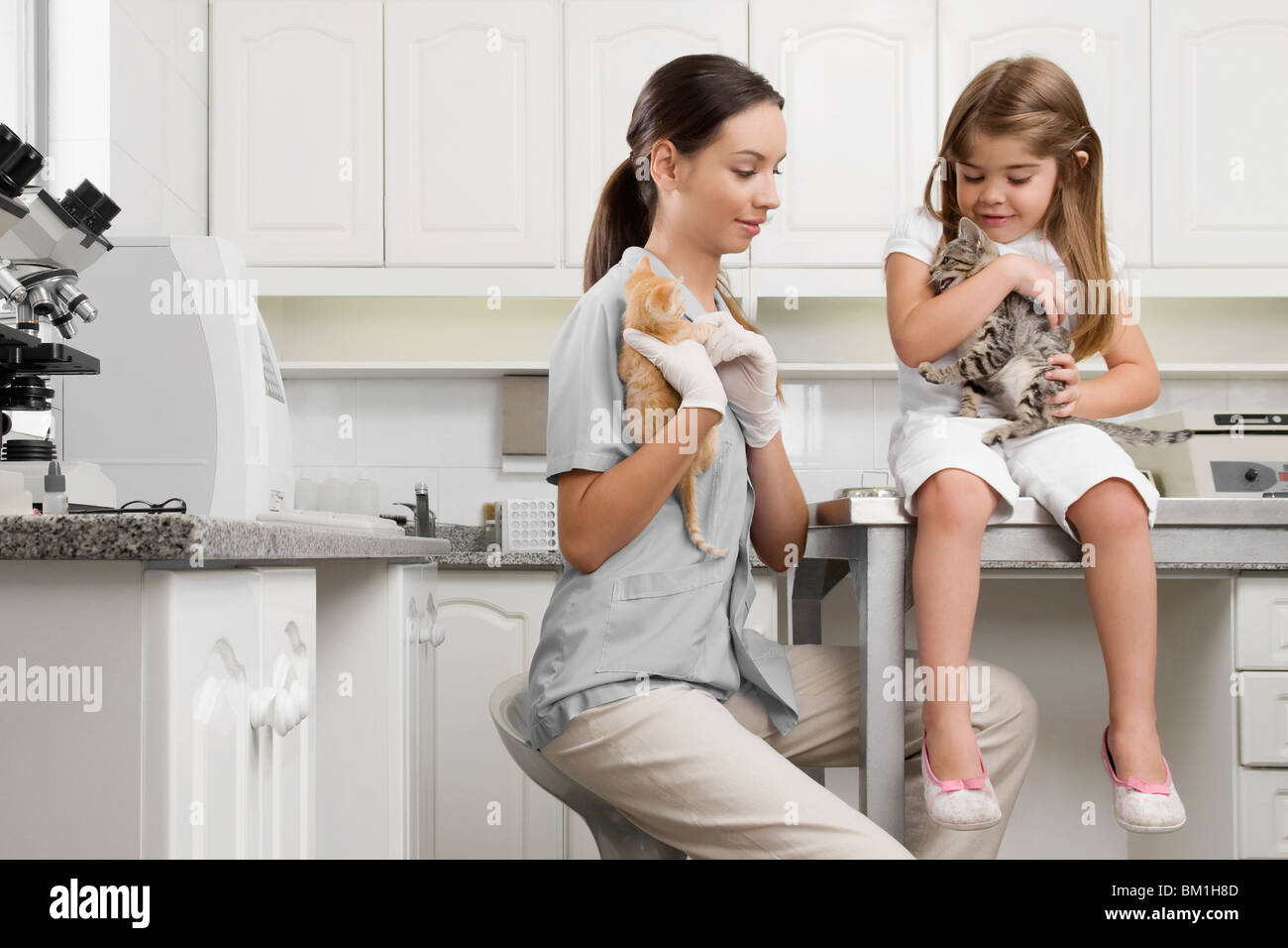 Female vet with a girl carrying cats - Stock Image