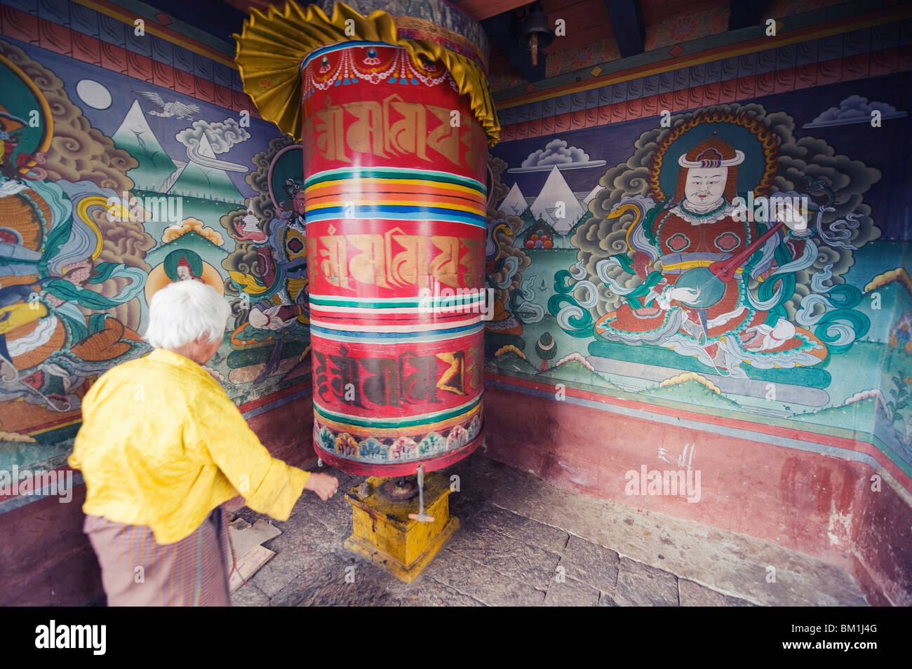 A woman spinning prayer wheel, Chimi Lhakhang dating from 1499, Temple of the Divine Madman Lama Drukpa Kunley, - Stock Image