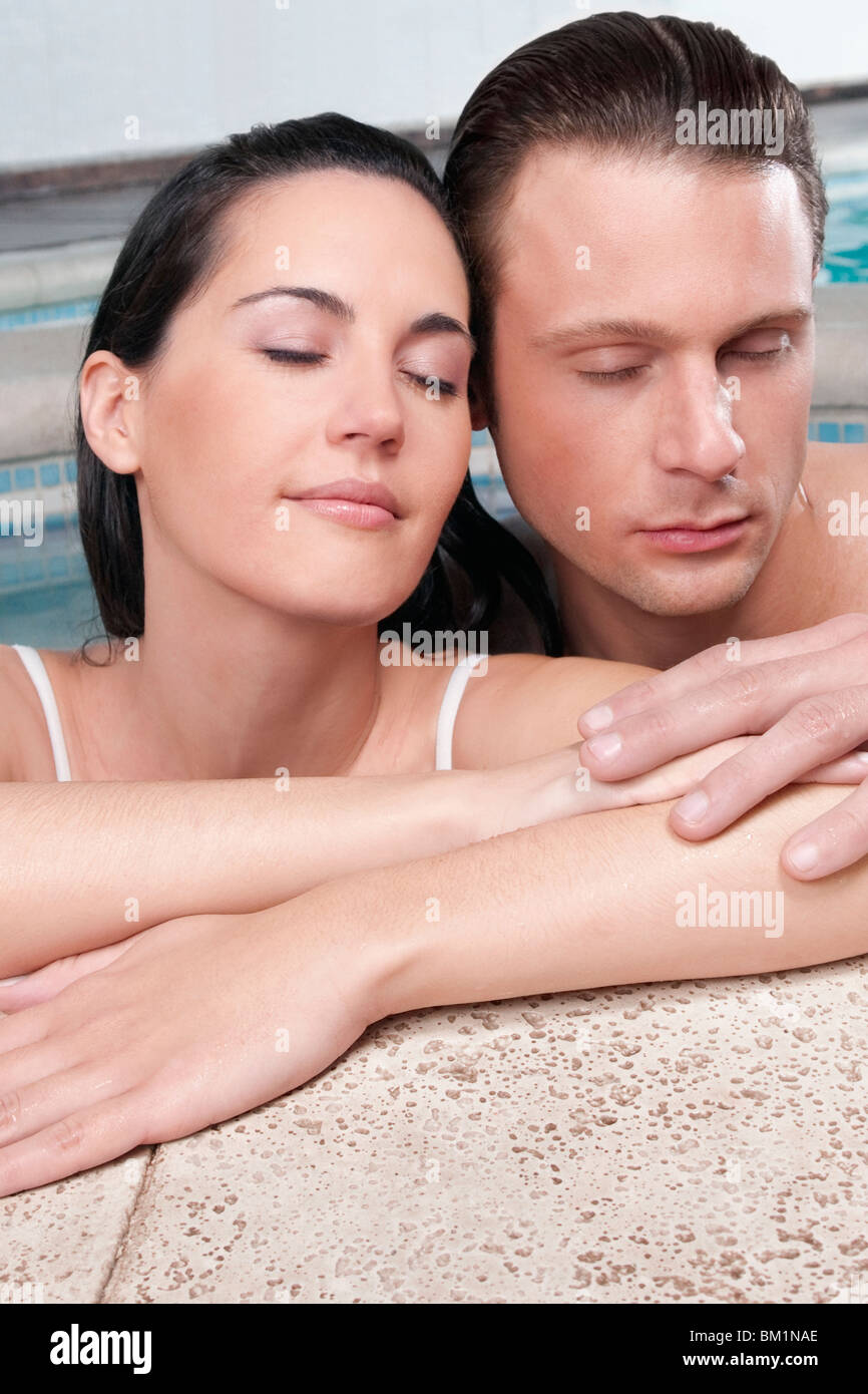 Couple romancing in a hot tub - Stock Image