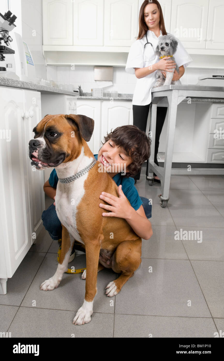 Boy hugging a dog with a vet in the background Stock Photo