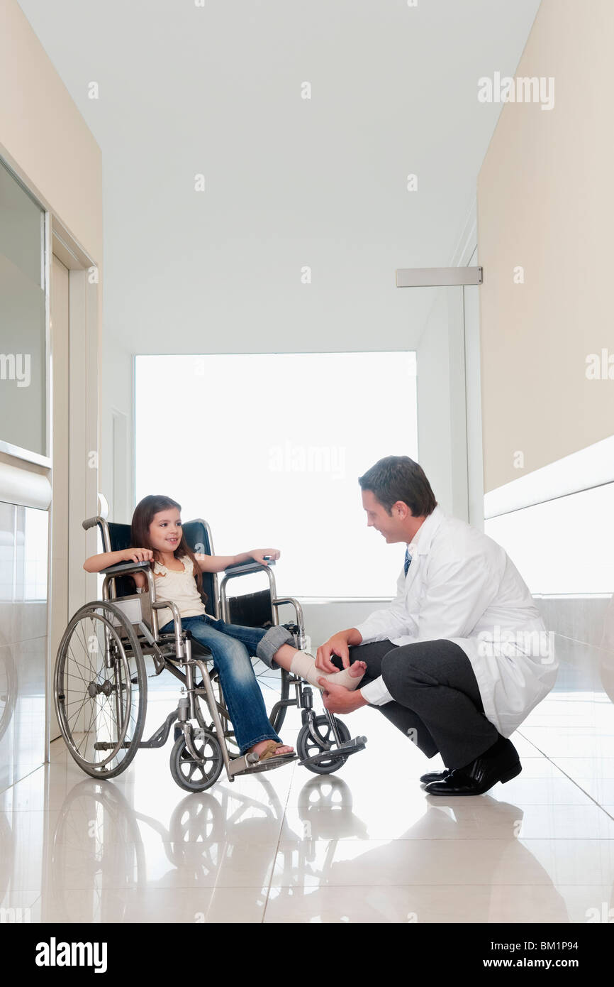 Doctor examining a patient's leg in a hospital corridor - Stock Image